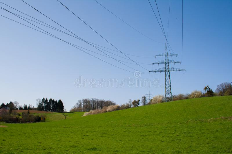 Utility pole in green nature. Utility poles within a hilly green nature in the country royalty free stock image