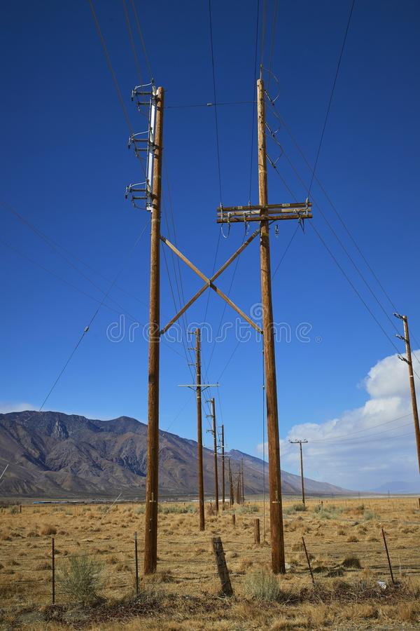 Utility poles in desert. Clear blue sky and mountains in distance. Line of utility power poles in desert. Clear blue sky with minimal clouds. Mountain in stock image