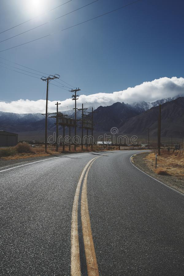 Utility power poles either side of road. Mountains and clear blue sky. Bitumen asphalt road curving to right. Multiple Utility power poles to left of road royalty free stock image