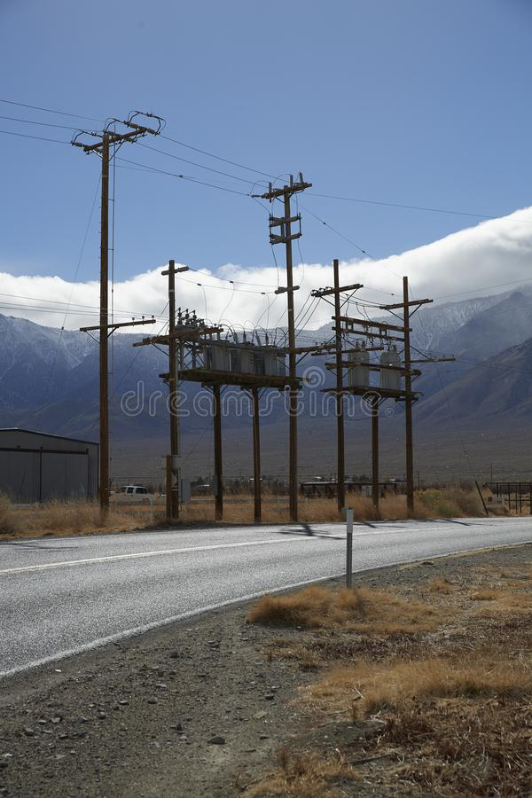 Utility power poles on side of road. Mountains and clear blue sky. Bitumen asphalt road curving to right. Multiple Utility power poles to left of road royalty free stock photography