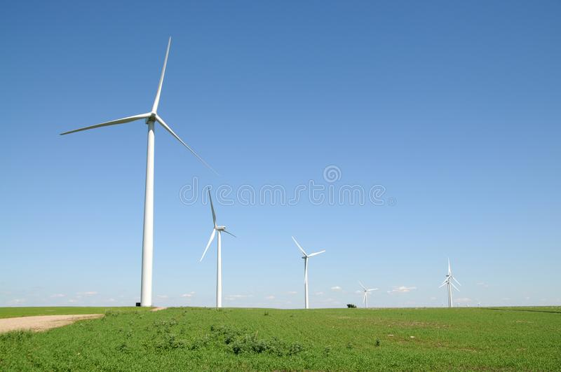 Utility windmills generating electricity. Utility windmills generate electricity on a sunny cloudless day alongside a rural dirt road royalty free stock photography