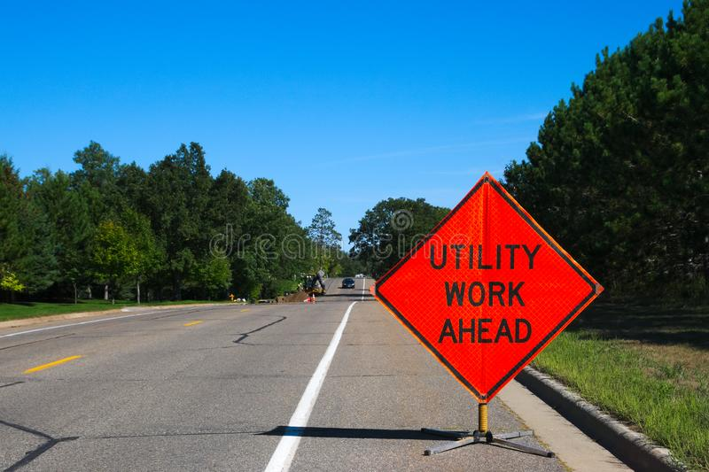 Utility Work Ahead sign with service vehicle on street. Utility Work Ahead sign with service vehicle down the street royalty free stock images