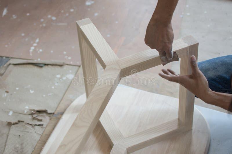 Utilización de madera de lija de papel de lija para la elaboración de la mesa, fotografía de archivo libre de regalías