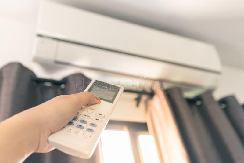 Utilizzi il telecomando per accendere il condizionatore d'aria fotografia stock libera da diritti