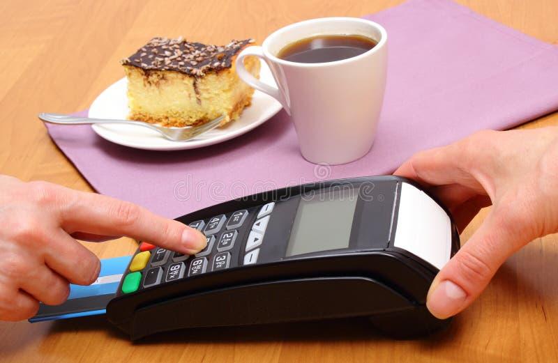 Utilizzi il terminale di pagamento per il pagamento la torta di formaggio ed il caffè in caffè, concetto di finanza fotografia stock libera da diritti