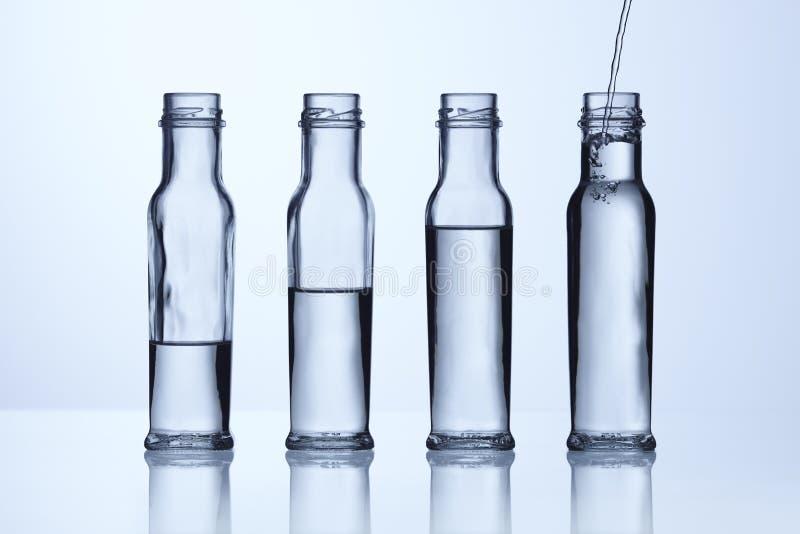 utjämniner olikt exponeringsglas för flaskan vatten royaltyfria bilder