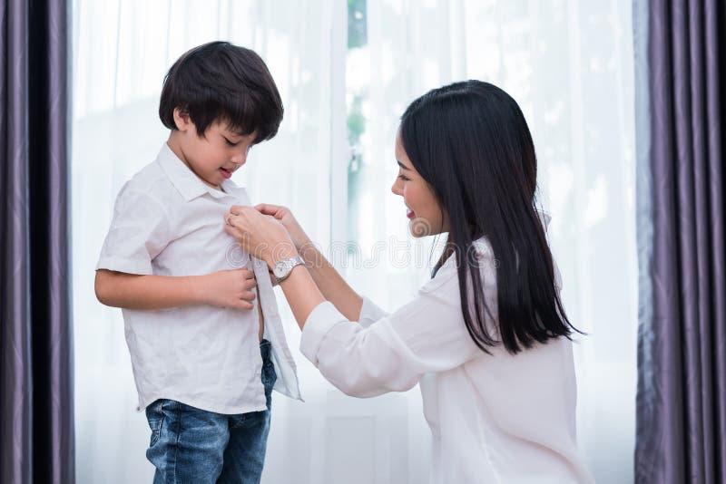 Utklädda sondräkter för ung asiatisk mamma för att förbereda sig att gå att skola Moder- och sonbegrepp Lycklig familj och hem- s royaltyfri foto