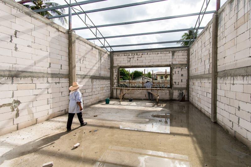 Utländska arbetare arbetar i konstruktionsplatsen Migrerande arbetstagare är mycket populära i konstruktion Becau royaltyfria bilder