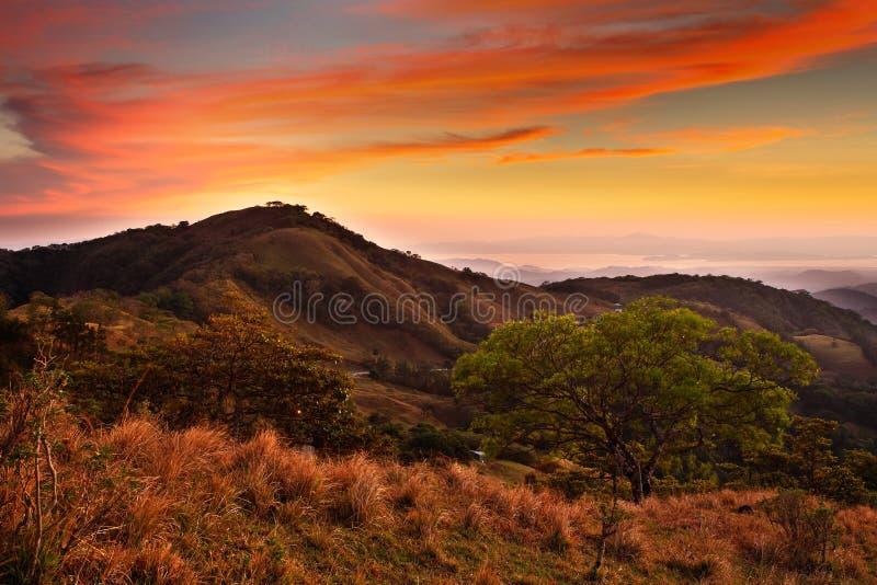 Utlöpare av det Monteverde molnet Forest Reserve, Costa Rica Vändkretsberg efter solnedgång Kullar med härlig orange himmel med c royaltyfri foto