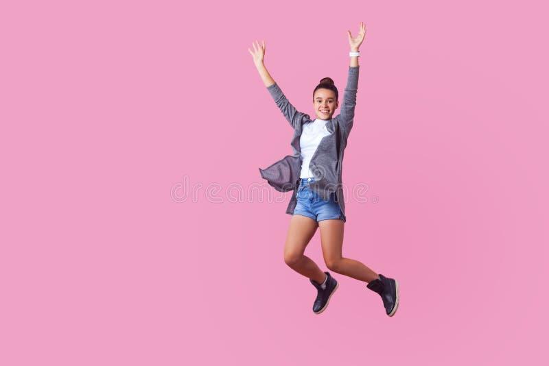 Utmärkt, energisk brunetstensflicka som hoppar i luften med entusiastiskt lyckligt ansikte och upphöjda händer, optimistiskt liv  arkivfoton
