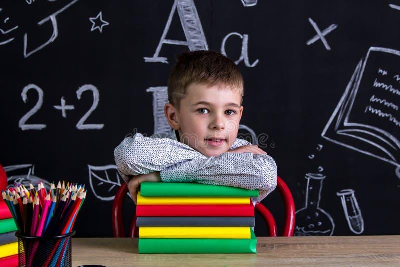 Utmärkt gulligt skolpojkesammanträde på skrivbordet med en hög av böcker under hakan som omges med skolatillförsel fotografering för bildbyråer