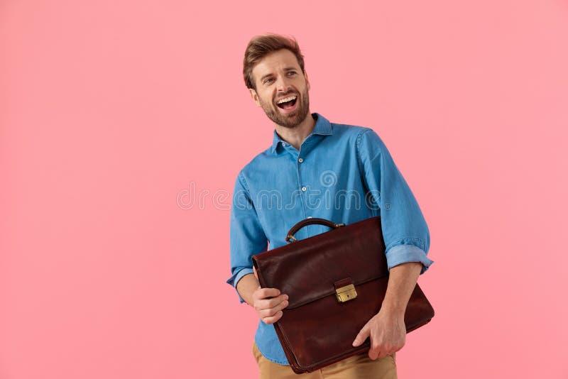 Utmärkt kille som håller resväska och skrattar royaltyfria foton