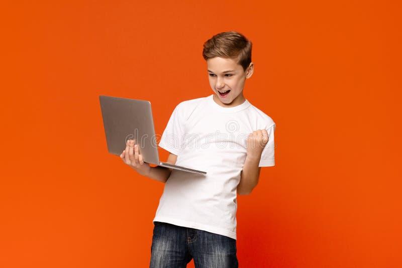 Utmärkt pojke som använder en bärbar dator och firar framgången royaltyfri foto
