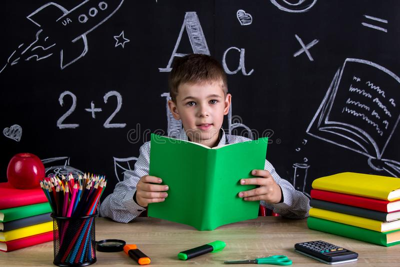 Utmärkt skolpojkesammanträde på skrivbordet som läser boken som omges med skolatillförsel som ser raka till arkivfoton