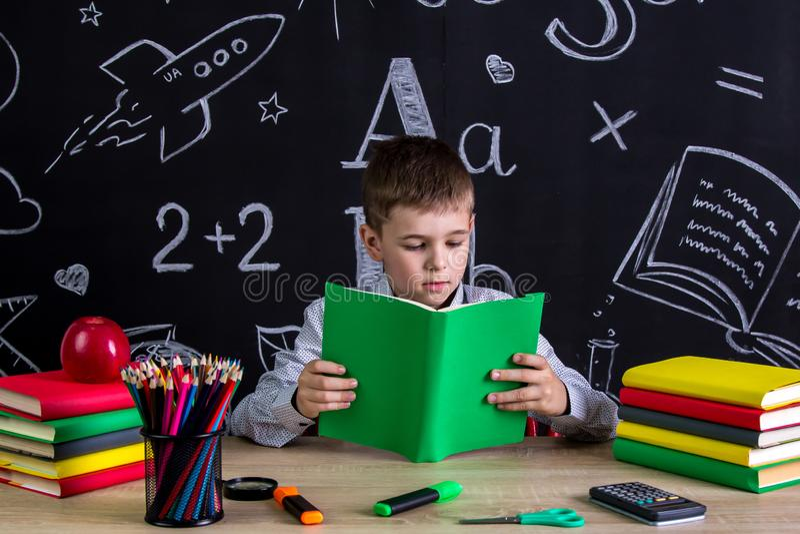 Utmärkt skolpojkesammanträde på skrivbordet som läser boken som omges med skolatillförsel Svart tavla som en bakgrund royaltyfria foton