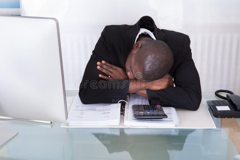 Utmattad affärsman på skrivbordet royaltyfri fotografi