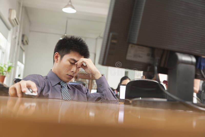 utmattad affärsman som framme sitter av datoren royaltyfria foton