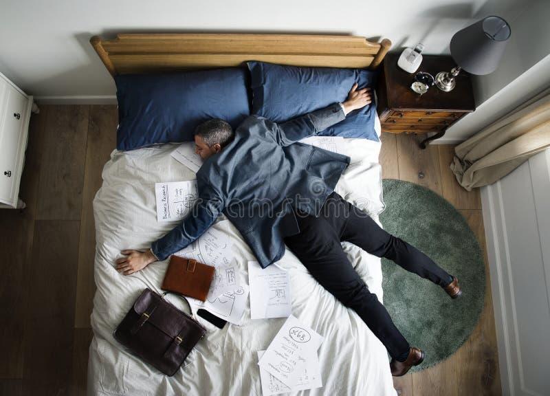 Utmattad affärsman som sovande faller, så snart som han kom tillbaka hem royaltyfria bilder