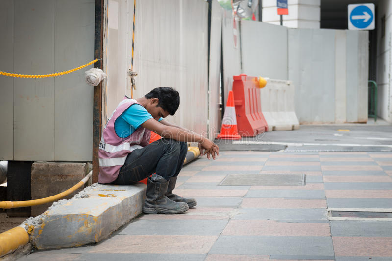 Utmattad byggnadsarbetare Takes ett avbrott i Singapore royaltyfria bilder