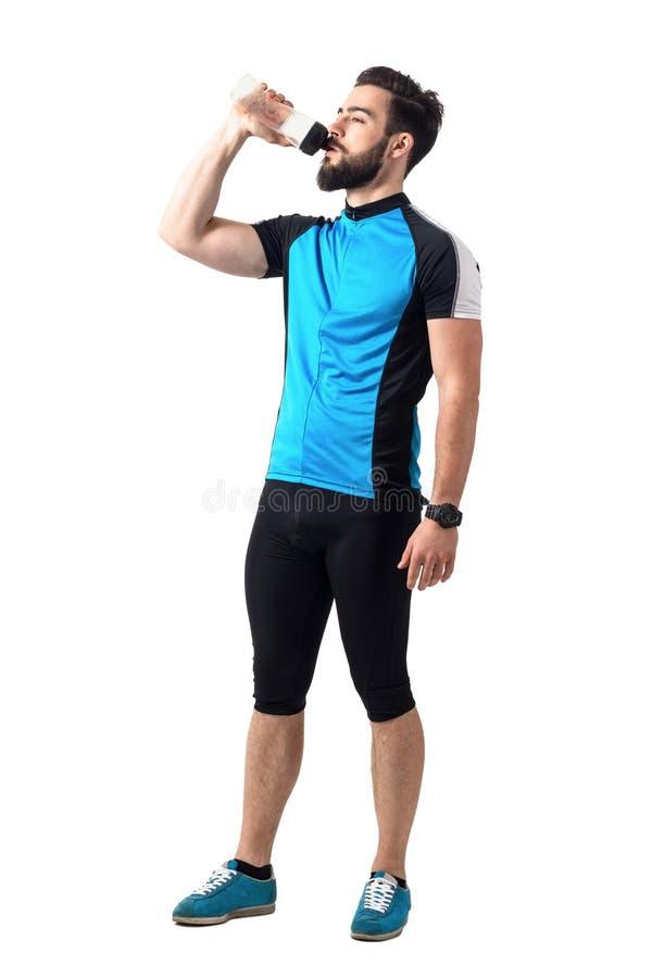 Utmattad idrottsman nen, i att cykla sportsweardricksvatten från den plast- flaskan fotografering för bildbyråer