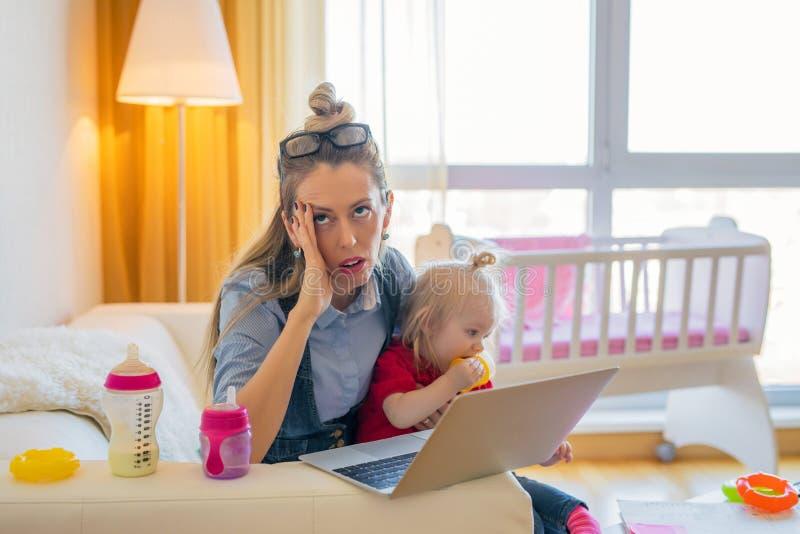 Utmattad kvinna med det lilla barnet royaltyfri foto