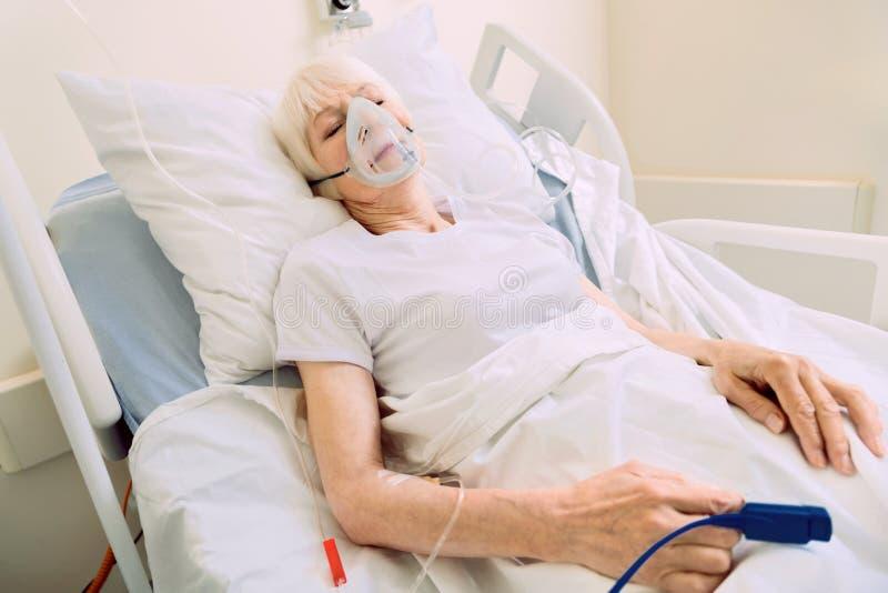 Utmattad kvinna som ligger i säng med den respiratoriska maskeringen arkivfoto