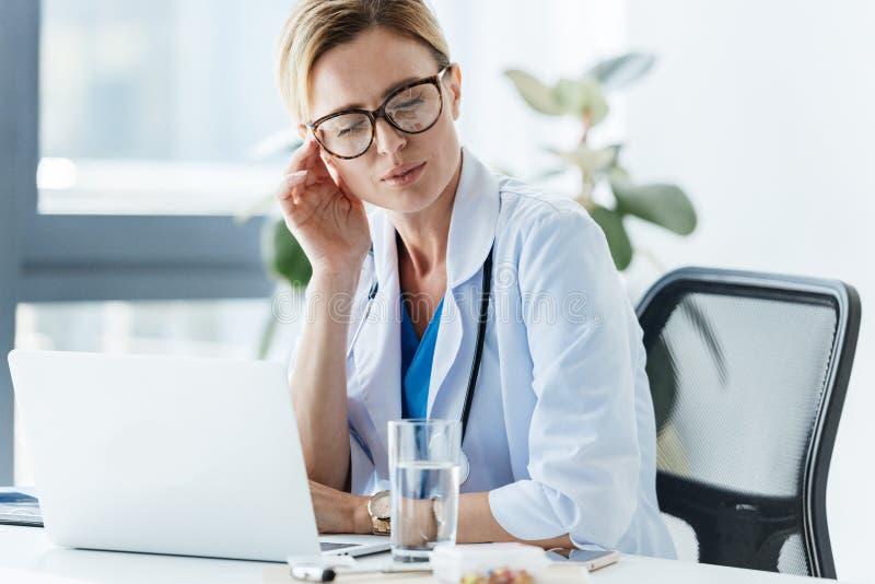 utmattad kvinnlig doktor i glasögon som har huvudvärk på tabellen arkivbilder