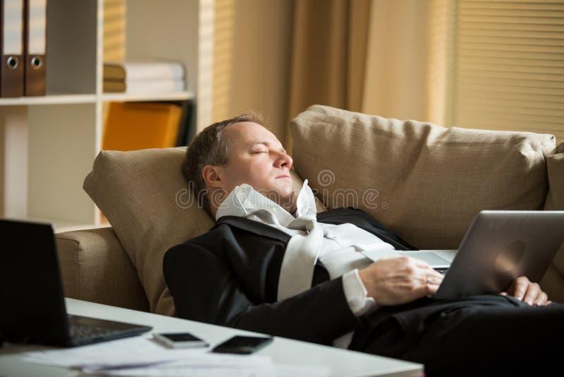 Utmattad man i regeringsställning arkivfoto
