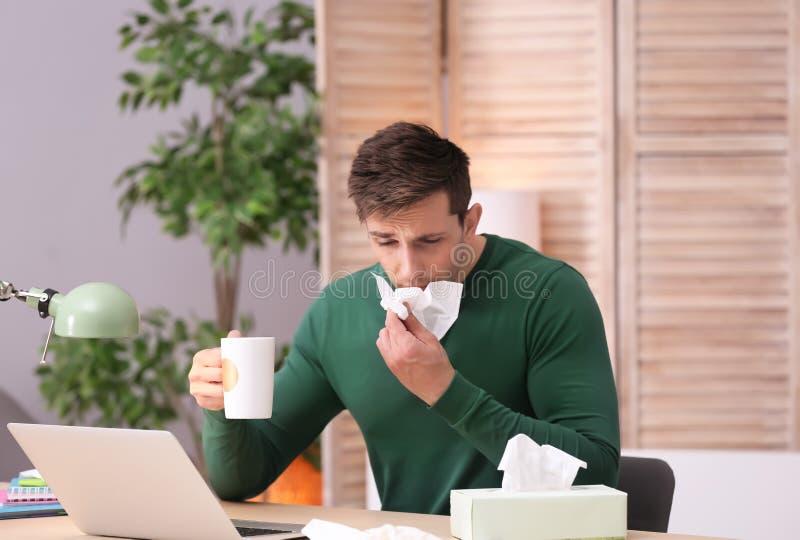 Utmattad man med silkespappret och kopp av varmt drinklidande från förkylning, medan arbeta med bärbara datorn på tabellen arkivfoton