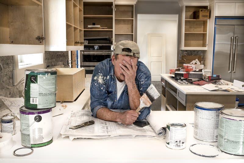 Utmattad och trött målare med framsidan i händer som överallt rymmer den våta målarfärgborsten i smutsigt hem- kök med målarfärgc royaltyfri bild