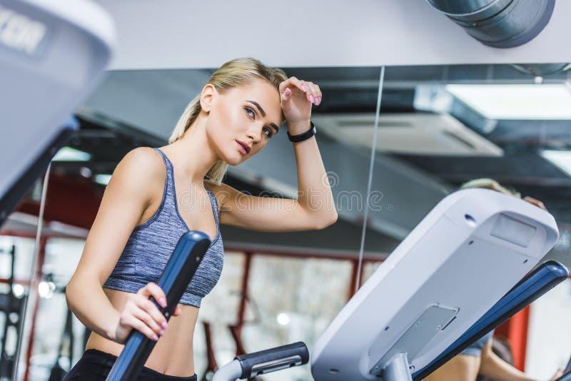 utmattad sportive kvinna som utarbetar på den ellipsformiga maskinen arkivfoton