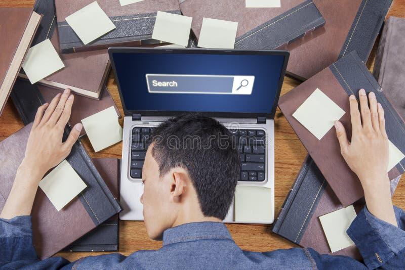Utmattad student- och webbläsaresida på bärbara datorn arkivbilder