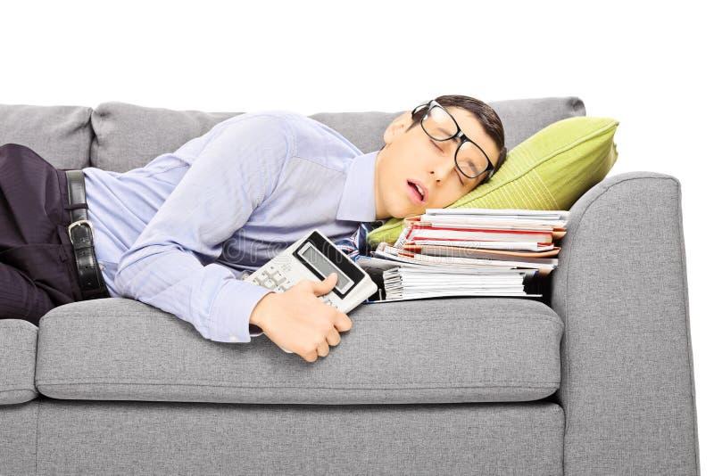 Utmattad ung affärsman som sover på en soffa med många docume arkivbild