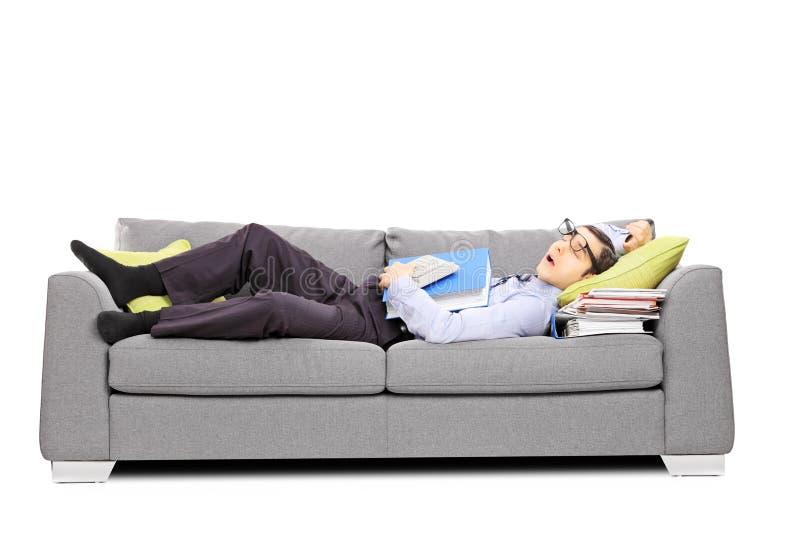 Utmattad ung revisor som sover på en soffa arkivfoto