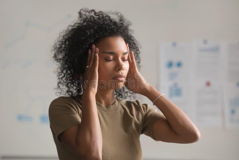 Utmattade tempel för massage för svart kvinnaarbetare som har huvudvärk arkivfoton