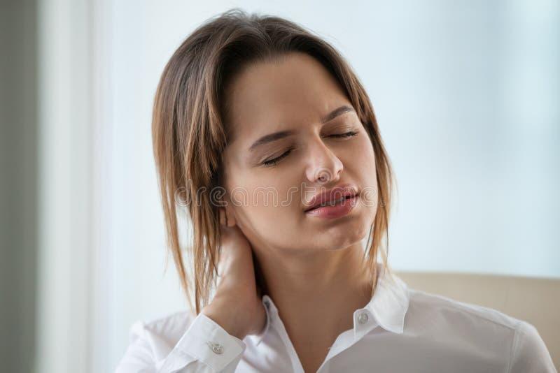 Utmattat lidande för affärskvinnamassagehalsen från muskeln smärtar arkivbild