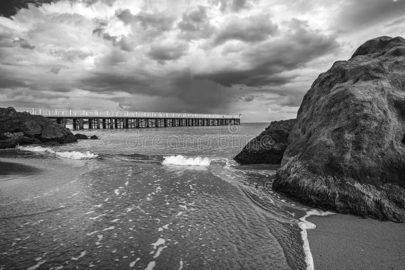 Utmed vågor mellan stora stenar på stranden royaltyfri fotografi