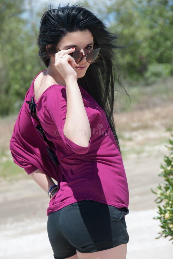Utomhus- av ett mode som är tonårigt med kortslutningar och solglasögon arkivfoto