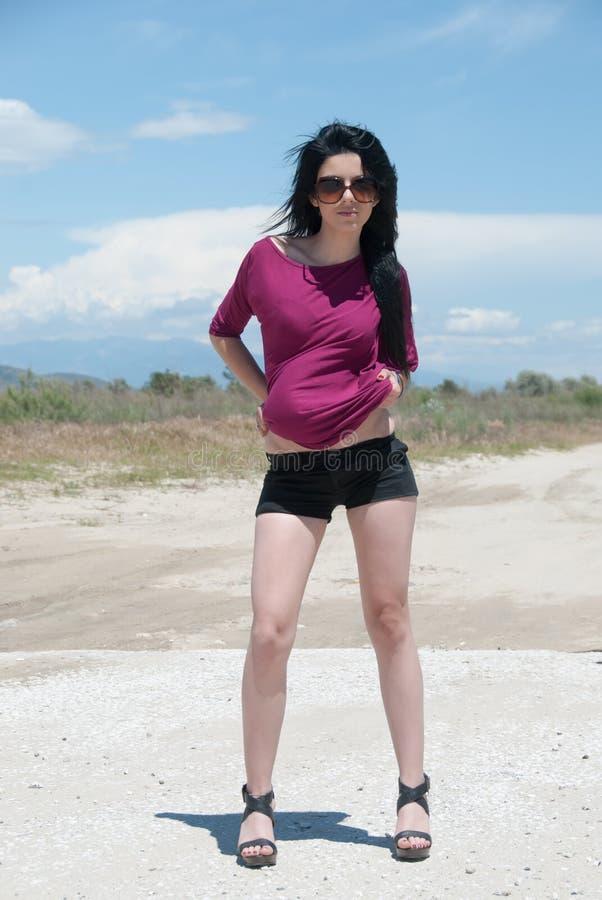 Utomhus- av ett mode som är tonårigt med kortslutningar och solglasögon arkivbild