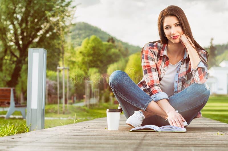 Utomhus- avkopplingbegrepp med den härliga kvinnan som läser en bok arkivfoton
