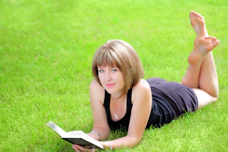 Utomhus- bild av den älskvärda deltagareflickan med boken royaltyfri fotografi