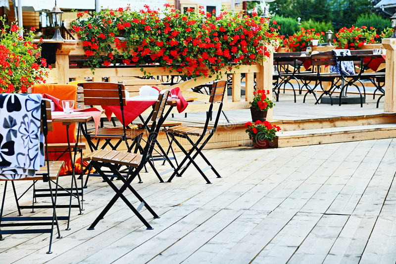 utomhus- cafe Stolar och tabeller på terrassen med blommor royaltyfria foton