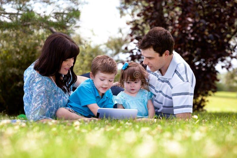 Utomhus- familj med den Digital tableten royaltyfria foton