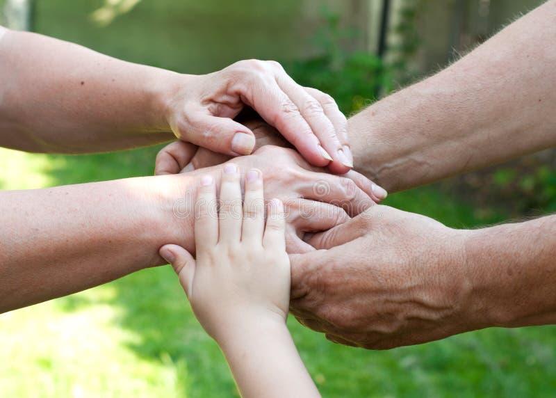 Utomhus- familjinnehavhänder tillsammans royaltyfria foton