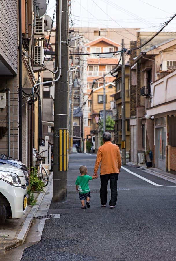 Utomhus- foto av den äldre mannen som går med det unga lilla barnet på gatan i Kyoto, Japan arkivbilder
