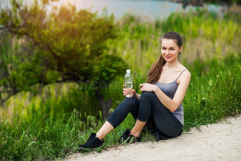 Utomhus- foto av den nätta unga kvinnan som bär sportive kläder och arkivbilder