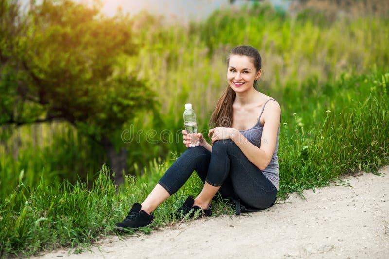 Utomhus- foto av den nätta unga kvinnan som bär sportive kläder och royaltyfria bilder