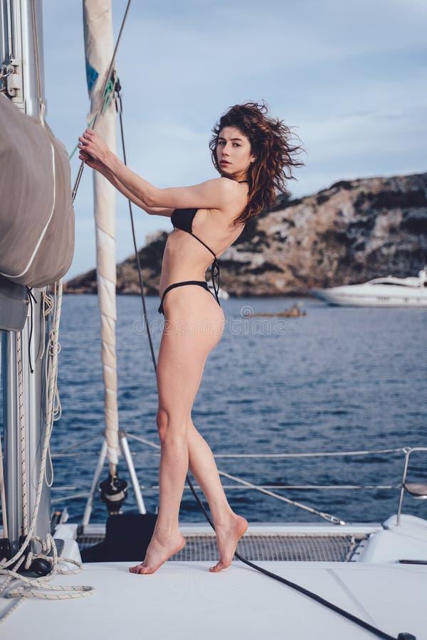 Utomhus- foto för mode av den härliga unga kvinnan som poserar på yachter royaltyfri foto