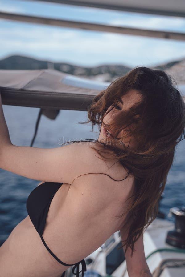 Utomhus- foto för mode av den härliga unga kvinnan som poserar på yachter royaltyfria bilder