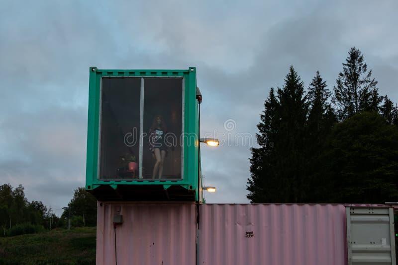 Utomhus- främre fasadnattsikt av för behållarehem för två våning en byggnad med ett stort fönster i Sverige arkivfoto